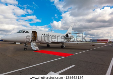 White reactive jet, the front landing gear and gangways on blue sky and clouds - stock photo