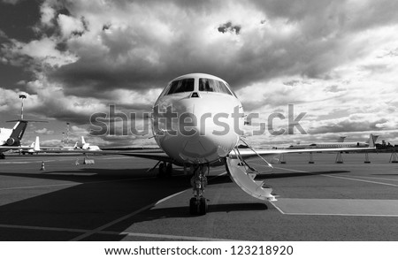 White reactive private jet, the front landing gear and gangways - stock photo