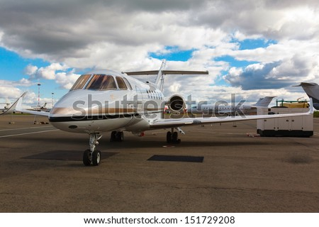 White reactive private jet, the front landing gear on blue sky and clouds - stock photo