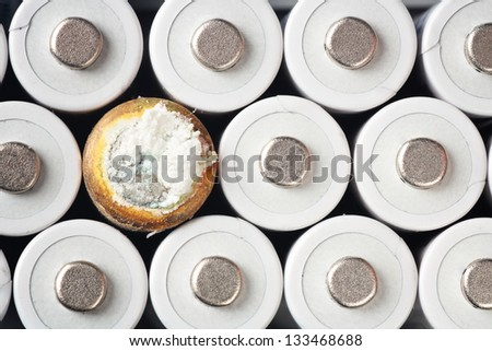 White rechargeable batteries and a rusty one - stock photo