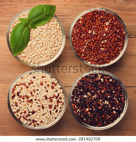 White, red, black and mixed raw quinoa, South American grain, in glass bowls on old rustic woodenbackground. Top view. Toned. - stock photo