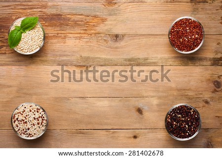 White, red, black and mixed raw quinoa, South American grain, in glass bowls with basil leaves on old rustic wooden background. Top view. Background with copy space. - stock photo