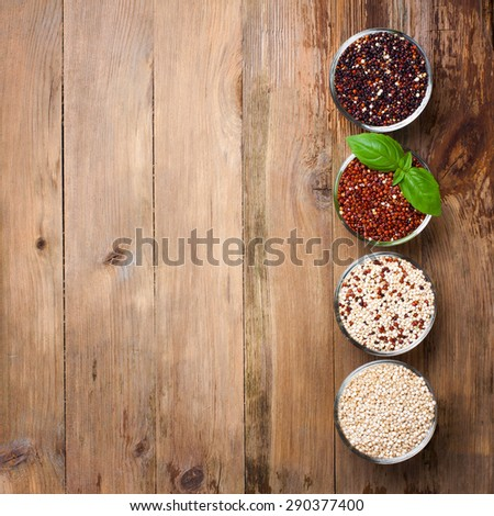White, red, black and mixed raw quinoa, South American grain, in glass bowls with basil leaves on old rustic wooden background. Top view. Background with copy space. Healthy food concept. - stock photo