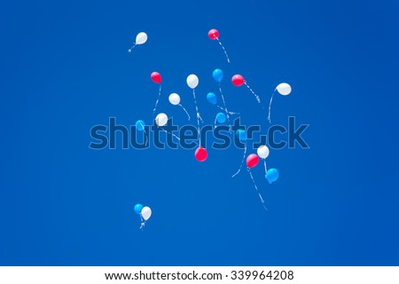 white red blue balloons on a blue sky background white red unfocused - stock photo