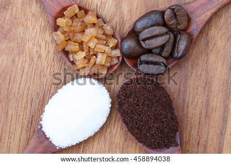 White, red sugar, coffee powder and coffee beans in wooden spoon on wooden background. - stock photo