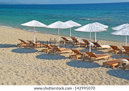 white reed umbrellas chairs sunbeds blue sea holidays  - stock photo