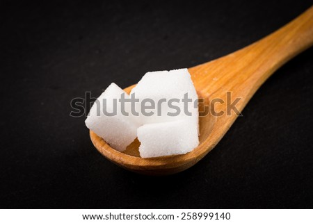 White refined sugar in wooden spoon on dark stone background - stock photo
