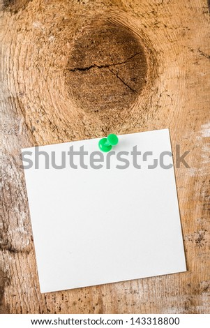 White reminder note with shade and green pushpin on wooden brown  background. Add your own text or design