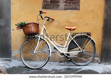 White retro bicycle with wicker brown basket standing at the wall, Italy - stock photo