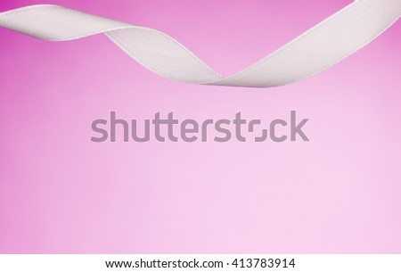 White ribbon isolated on a pink, pastel background. Product photograph taken in the studio on seamless paper background. - stock photo