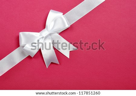 White ribbon with bow on a pink background - stock photo