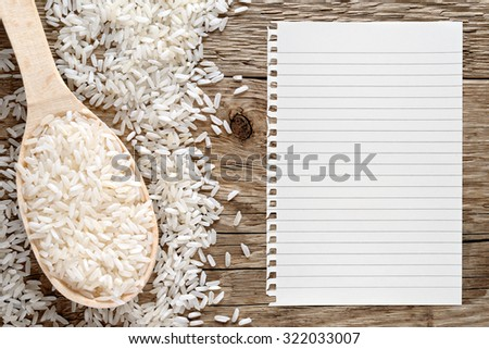 White rice and paper for recipe on wooden background