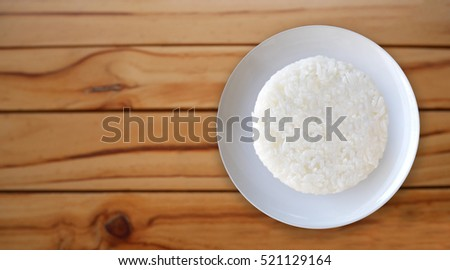 White rice circle shape in a ceramic dish on wood background