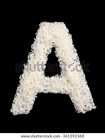 White rice grain alphabet letter isolated on black. - stock photo