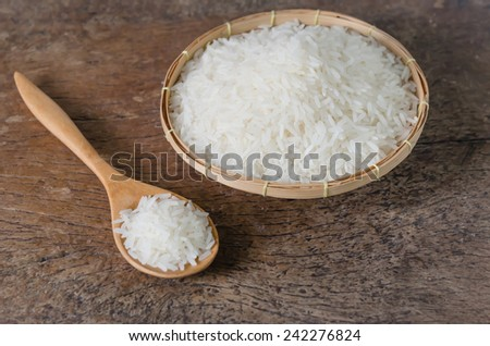 white rice  grains with wooden spoon on wooden table - stock photo