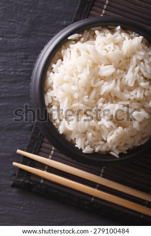 White rice in a black bowl close-up and chopsticks. vertical top view  - stock photo