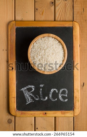 White rice in a wooden bowl on a chalkboard with the words - stock photo