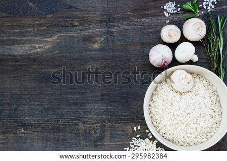 White rice in bowl with ingredients for risotto on dark wooden background with space for text. Vegetarian food, health or cooking concept. - stock photo
