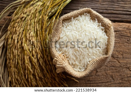 white rice in burlap sack with rice grain - stock photo