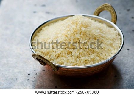 white rice in the Indian copper bowl on a metal background. selective focus. - stock photo