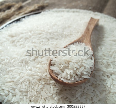 White rice in the wooden spoon and on rice background