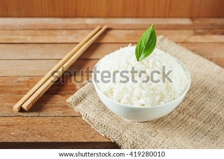 White rice in white bowl with wooden chopsticks on wooden background, Still life tone - stock photo