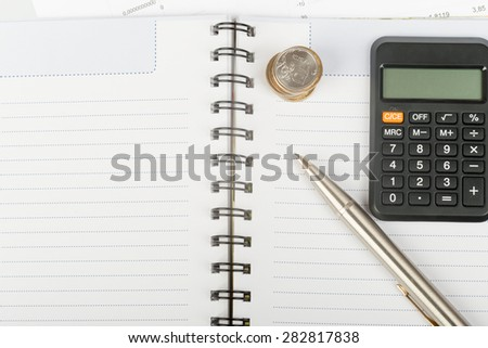 White ring-bound notebook with coins, close-up view