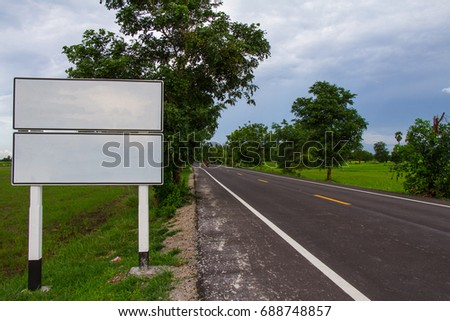 White Road sign on green field