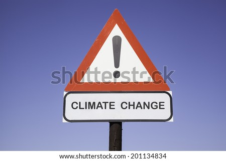 White road warning triangle with black  exclamation point and red frame on  a wooden mast in front of a blue sky. A second rectangular sign warns in english about climate change - stock photo