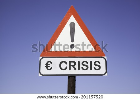 White road warning triangle with black  exclamation point and red frame on  a wooden mast in front of a blue sky. A second rectangular sign warns in english about  Euro crisis - stock photo