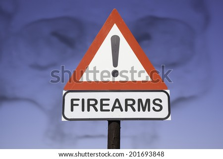 White road warning triangle with black  exclamation point and red frame on  a wooden mast in front of a blue sky wiith the shadow of a skull. A second rectangular sign warns in english about firearms - stock photo
