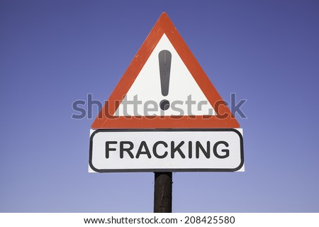 White road warning triangle with black  exclamation point and red frame on  a wooden mast in front of a blue sky. A second rectangular sign warns in english about fracking - stock photo