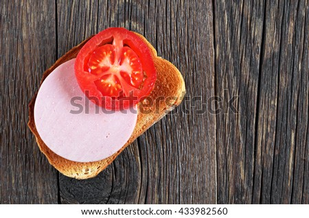 White roasted bread with boiled sausage and tomato on wooden table, top view