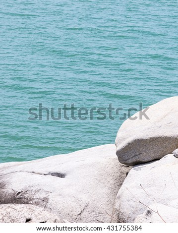 White rock cliff near the clear blue sea in the southern of Thailand. - stock photo