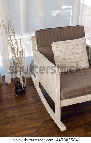 white rocking chair with brown cushion in the interior - stock photo