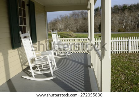 White Rocking Chairs on Front Porch with Picket Fence - stock photo