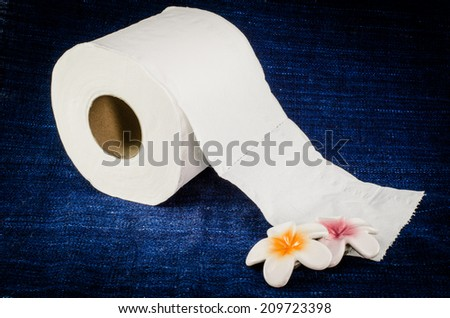 White roll tissue on deep blue fabric - stock photo