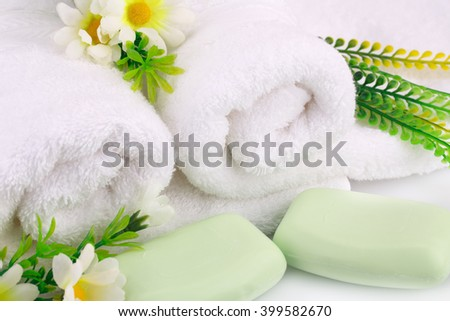 White rolled towels with soaps and flowers closeup picture. - stock photo