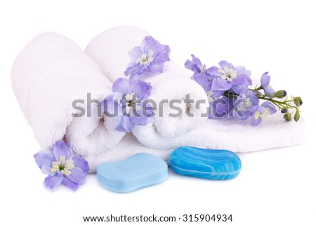 White rolled towels with soaps and flowers isolated on white background. - stock photo