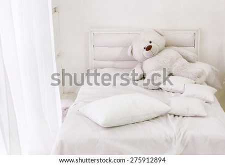 white room corner with bed teddy bear and window with white curtain - stock photo