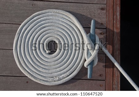 White rope coiled on a wooden dock and tied to a metal dock cleat.  Cleats are used for securing docks and lines from boats - stock photo