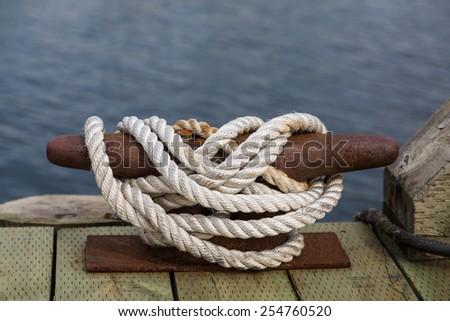 White rope secured to an old rusty cleat on a wood pier - stock photo