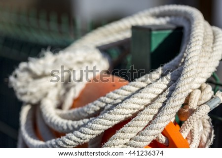 White rope tied to orange float used by lifeguards at swimming pool or beach - stock photo