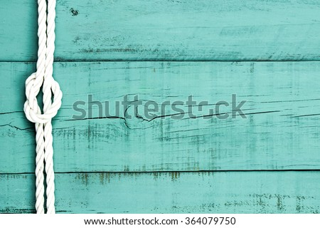 White rope with knot on blank antique mint green rustic wood background - stock photo