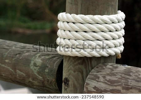 White rope wrapped around dock pier post - stock photo