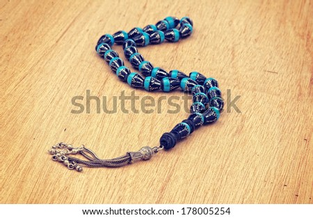White Rosary laying on a wooden background with retro filter effect  - stock photo