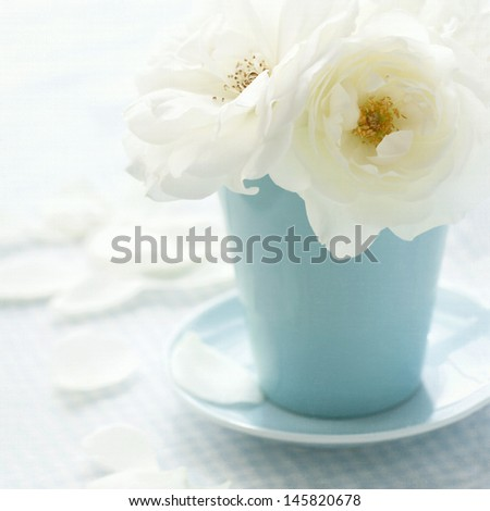 White rose in a light blue vase on shabby chic vintage background - stock photo