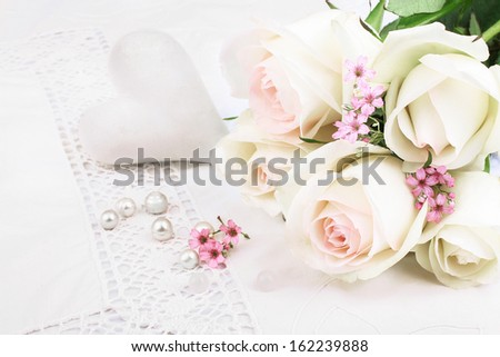 White roses and heat on tablecloth - stock photo