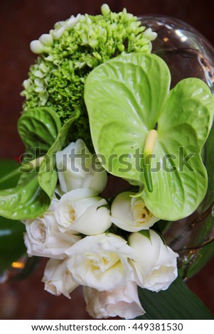 White roses and troppical leafs in a vase - stock photo