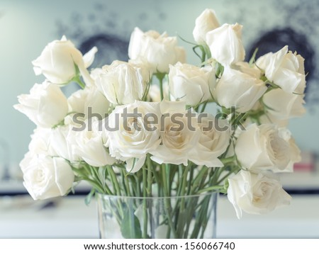 White roses in a glass vase - stock photo